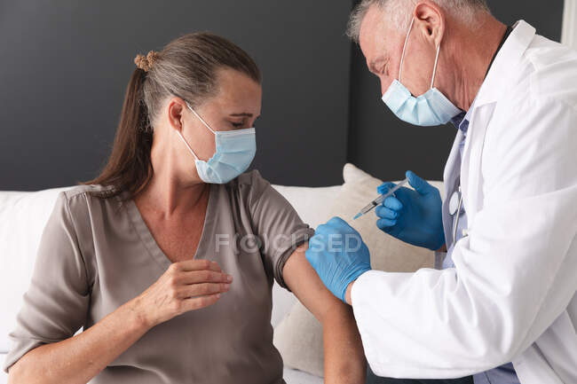Médico varón mayor caucásico que administra la vacuna covid 19 al paciente femenino, ambos con máscaras faciales. profesional médico en el trabajo durante la pandemia del coronavirus covid 19. - foto de stock