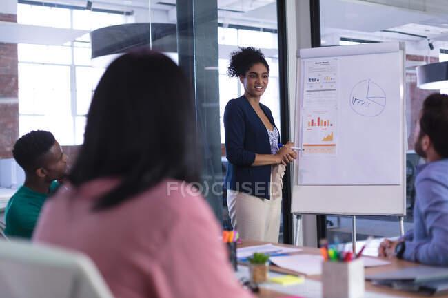 Змішана расова жінка, що стоїть на білому дошці, дає презентацію різним колегам. Незалежний бізнес творчого дизайну. — стокове фото