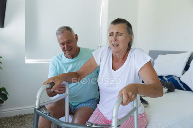 Caucasian senior couple sitting on bed, husband helping wife stand using walking frame. staying at home in isolation during quarantine lockdown. — Stock Photo