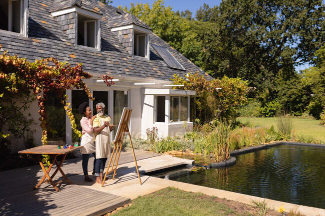 Улыбающаяся африканская старшая пара рисует картину вместе в солнечном саду. оставаться дома в изоляции во время карантинной изоляции. — стоковое фото