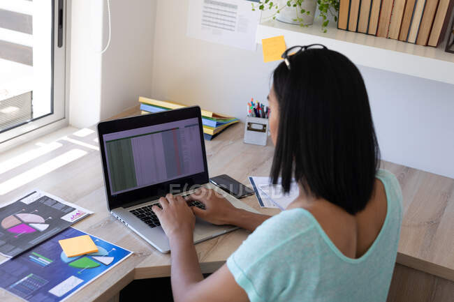 Mixed race transgender female working at home using laptop. staying at home in isolation during quarantine lockdown. — Stock Photo