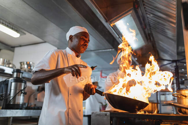 African american male professional chef flambeing dish in wok. working in a busy restaurant kitchen. — Stock Photo