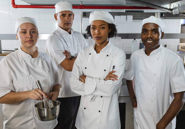 Portrait of diverse race male and female professional chefs. working in a busy restaurant kitchen. — Stock Photo