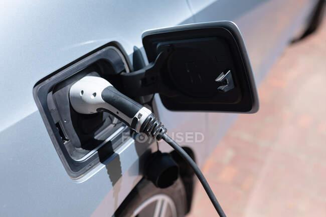 Gros plan de la voiture électrique rechargeable par fiche. préparation au voyage en voiture électrique hybride écologique. — Photo de stock
