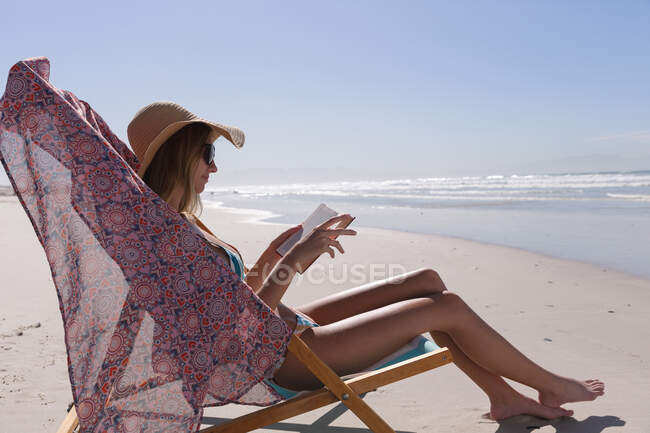 Caucasian woman wearing bikini sitting on deck chair reading book at the beach. healthy outdoor leisure time by the sea. — Stock Photo