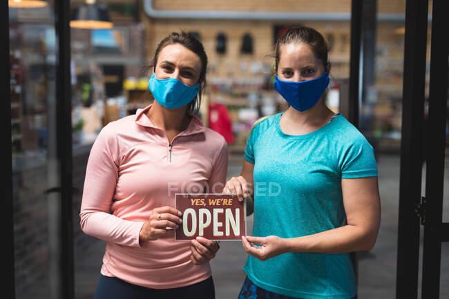 Retrato de dos mujeres caucásicas con máscaras sosteniendo un cartel abierto en el pasillo del gimnasio. fitness y tiempo libre en el gimnasio durante coronavirus covid 19 pandemia. - foto de stock