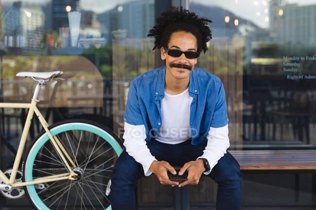 Ritratto di felice uomo misto di razza con baffi seduto su panchina in strada con smartphone. nomade digitale, in giro per la città. — Foto stock