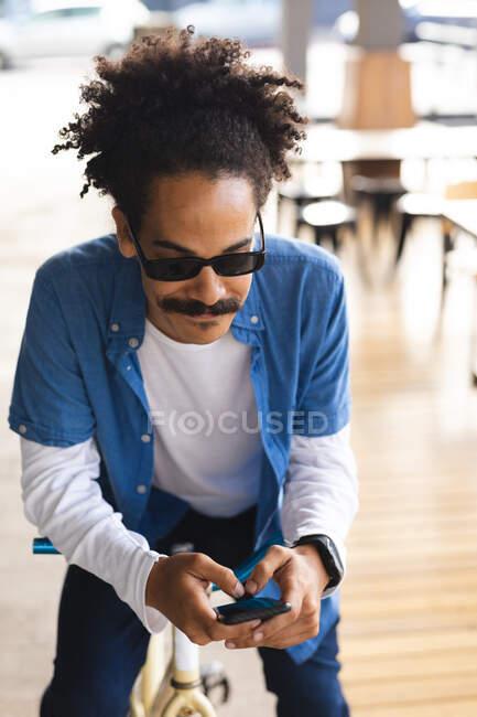 Homem de raça mista com bigode sentado na bicicleta na rua usando smartphone. nômade digital, para fora e sobre na cidade. — Fotografia de Stock