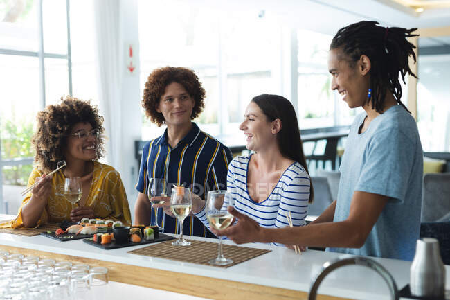 Diverse group of male and female colleagues having wine and sushi at bar. friends socialising and drinking at bar. — Stock Photo