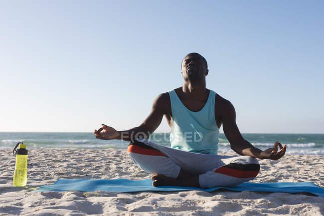 Африканский американец занимается на открытом воздухе, практикует йогу, медитирует на пляже. фитнес-тренировки. — стоковое фото