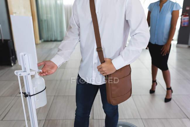 Parte central do homem caucasiano a desinfectar as mãos no átrio do hotel. hotel de viagens de negócios durante coronavírus covid 19 pandemia. — Fotografia de Stock