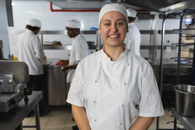 Portrait of Caucasian female professional chef with diverse colleagues in background. working in a busy restaurant kitchen. — Stock Photo