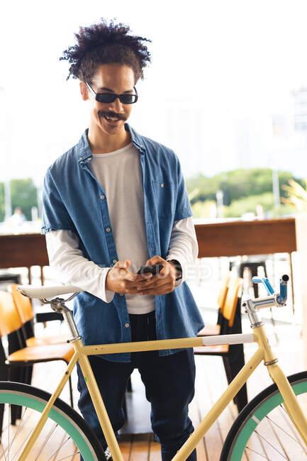 Щасливий чоловік змішаної раси з вусами стоїть на вулиці з велосипедом за допомогою смартфона. Цифровий кочівник, десь у місті.. — стокове фото
