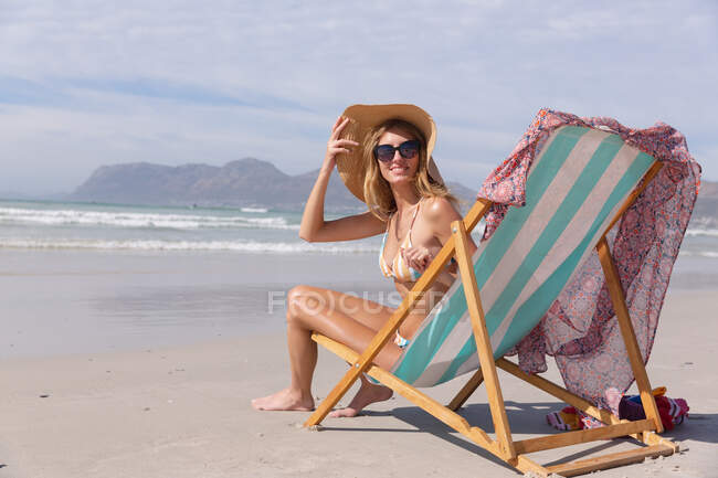 Smiling caucasian woman wearing bikini sitting on deck chair looking at camera at the beach. healthy outdoor leisure time by the sea. — стокове фото