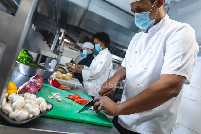 Diverse race male and female professional chefs preparing vegetables wearing face masks. working in a busy restaurant kitchen during coronavirus covid 19 pandemic. — Stock Photo