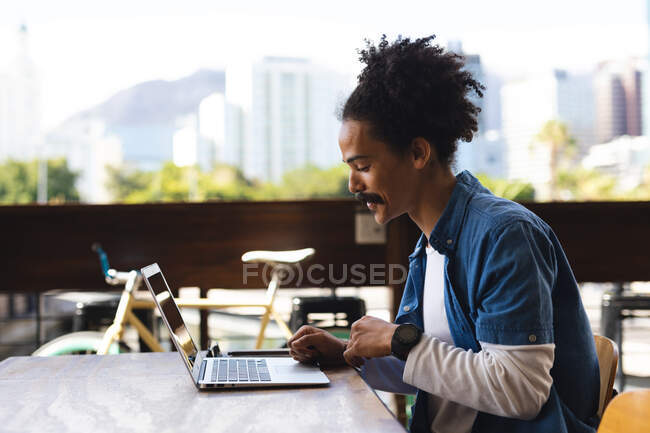 Smiling mixed race man with moustache sitting at table outside cafe using laptop. digital nomad, out and about in the city. — Stock Photo