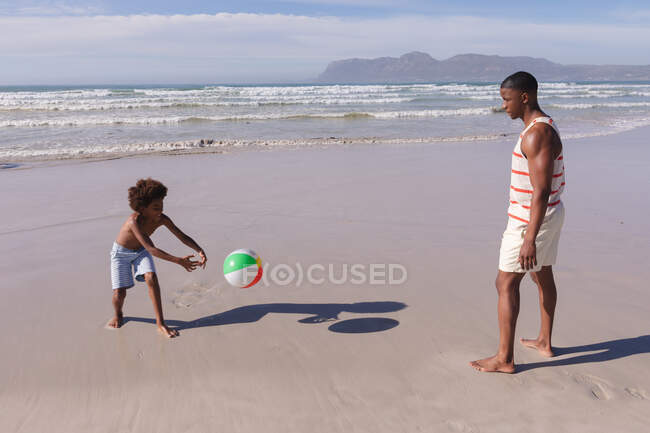 African american father and son having fun playing with ball at the beach. family outdoor leisure time by the sea. — Stock Photo