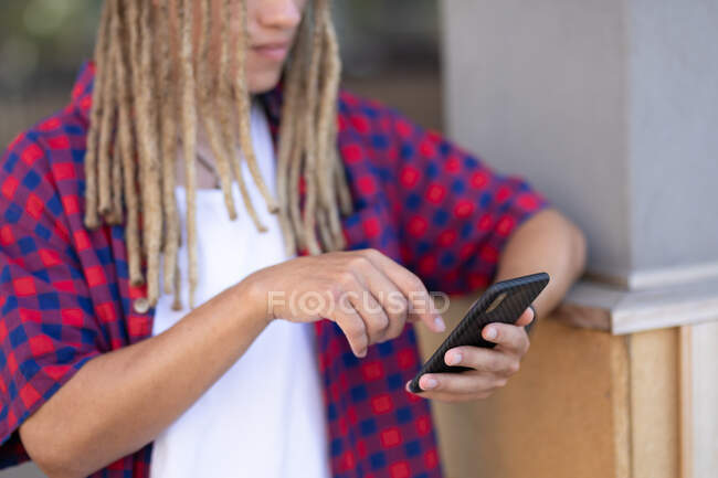 Mid section of mixed race male with dreadlocks using smartphone in the street. digital nomad, out and about in the city. — Stock Photo