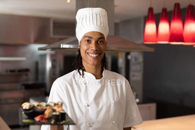 Portrait of mixed race professional chef wearing chefs hat serving sushi. chef at work in a modern restaurant kitchen. — Stock Photo