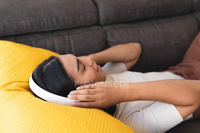 Щаслива міжрасова трансгендерна жінка відпочиває у вітальні лежачи на дивані з навушниками. Перебуваючи вдома в ізоляції під час карантину.. — стокове фото