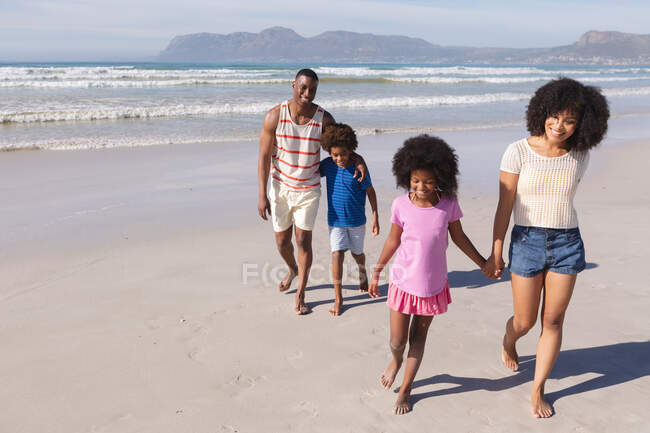 African american parents and two children smiling, walking and holding hands at the beach. family outdoor leisure time by the sea. - foto de stock