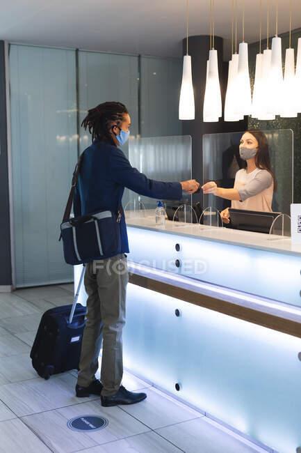 Diverso hombre de negocios con máscara facial hablando con la recepcionista en el hotel. viaje de negocios hotel durante coronavirus covid 19 pandemia. - foto de stock