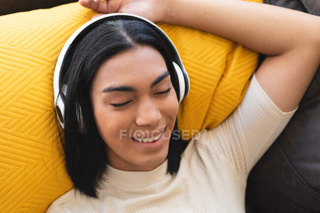 Happy mixed race transgender woman relaxing in living room lying on couch with headphones. staying at home in isolation during quarantine lockdown. — Stock Photo