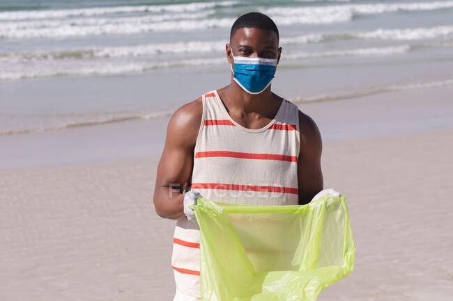 African american man wearing face mask collecting rubbish from the beach. eco beach conservation during coronavirus covid 19 pandemic. — Fotografia de Stock