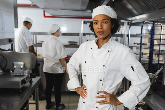 Portrait of mixed race female professional chef with colleagues in background. working in a busy restaurant kitchen. — Stock Photo