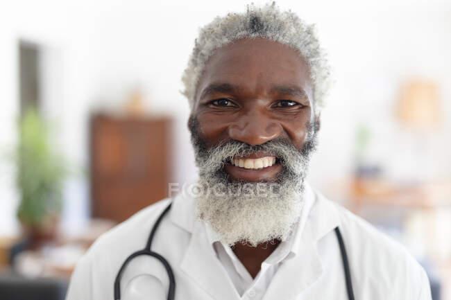 Ritratto di un anziano medico afro-americano sorridente che guarda la macchina fotografica. medico professionista sul lavoro. — Foto stock