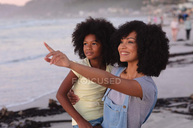 Smiling african american mother and daughter embracing at the beach, pointing. healthy outdoor leisure time by the sea. — Stock Photo