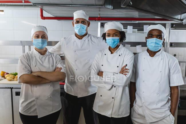 Retrato de diversas raças chefs profissionais masculinos e femininos em pé em máscaras faciais. trabalhando em uma cozinha restaurante ocupado durante coronavírus covid 19 pandemia. — Fotografia de Stock