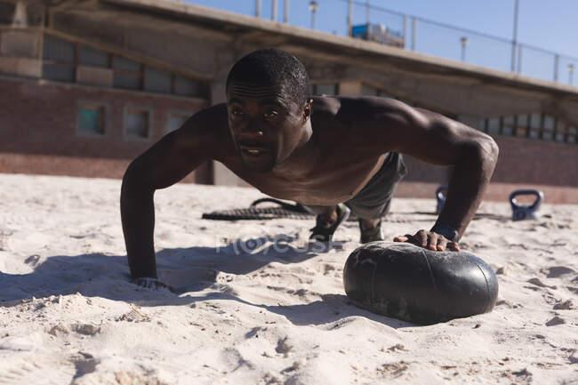Африканский американец, тренирующийся с гирями на пляже в солнечный день. фитнес-тренировки. — стоковое фото