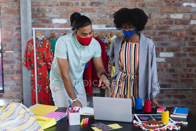Diversos diseñadores masculinos y femeninos mirando a la computadora portátil y hablando. negocio independiente de diseño de moda creativa durante coronavirus covid 19 pandemia - foto de stock