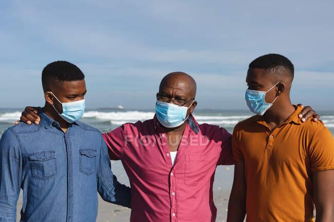 El padre afroamericano y sus dos hijos con máscaras en la playa. verano playa vacaciones reglas durante covid-19 pandemia concepto. - foto de stock