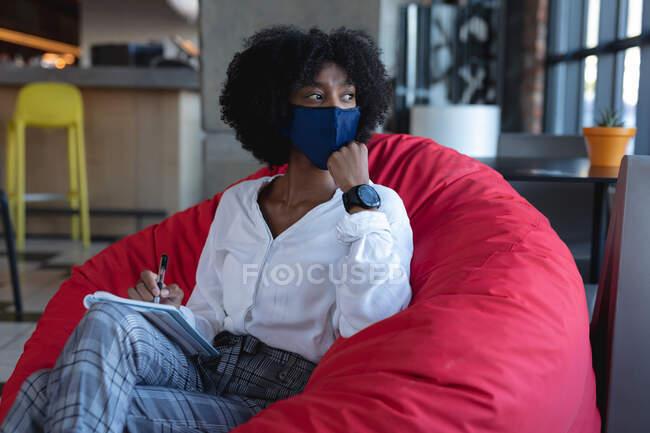 Mujer afroamericana usando mascarilla, sentada, tomando notas en el café. creativos digitales en movimiento durante la pandemia del coronavirus covid 19. - foto de stock