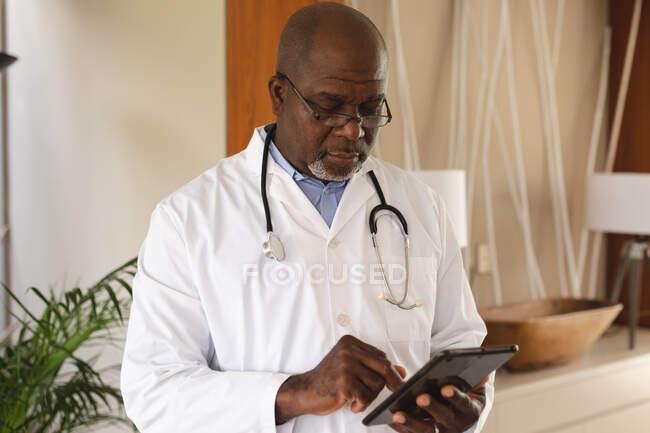 Medico afroamericano senior maschile che usa tablet digitale a casa. concetto di comunicazione a distanza e consultazione sulla telemedicina. — Foto stock