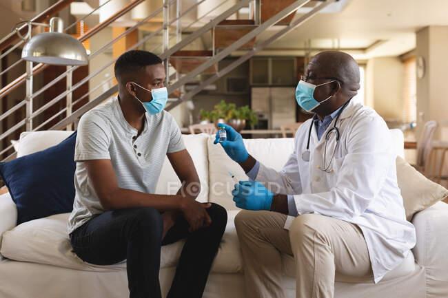 Médico afro-americano sênior mostrando garrafa de vacina covid-19 para homem afro-americano em casa. vacinação para prevenção do conceito de surto de coronavírus — Fotografia de Stock