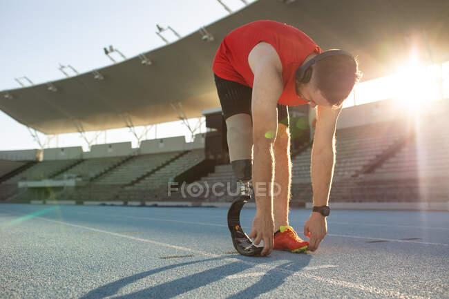 Кавказский спортсмен с протезной ногой выполняет упражнения на растяжку на беговой дорожке. Концепция паралимпийских игр — стоковое фото