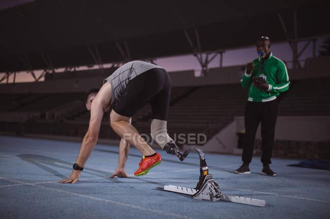 Кавказский спортсмен с протезной ногой в исходной позиции для бега по трассе ночью. Концепция паралимпийских игр — стоковое фото