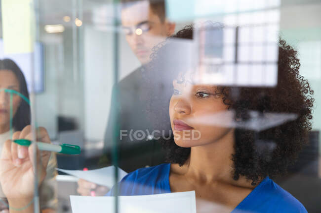 African american woman writing on glass board at modern office. business, professionalism and office concept — Stock Photo