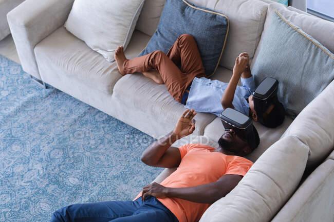 Африканский американец отец и сын лежат на диване в наушниках и трогают виртуальный экран. в доме в изоляции во время карантинной изоляции. — стоковое фото