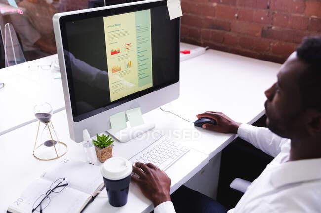 Hombre afroamericano usando la computadora mientras está sentado en su escritorio en la oficina moderna. negocio, profesionalidad y concepto de oficina - foto de stock