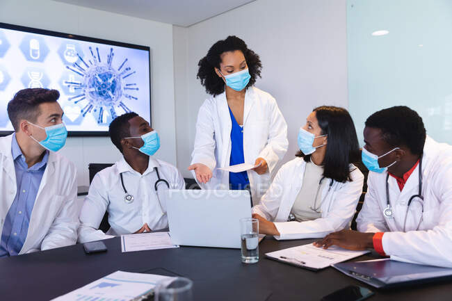 Team of diverse doctors wearing face mask discussing together over laptop in the meeting room. healthcare and medical research during covid 19 pandemic — Stock Photo