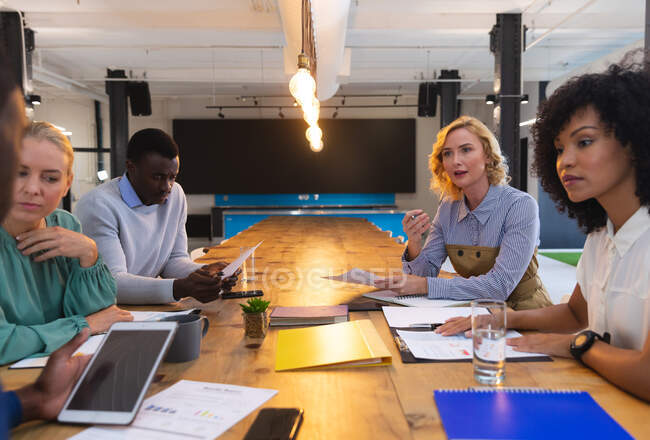 Team of diverse office colleagues discussing together at modern office. business, professionalism, office and teamwork concept — Stock Photo
