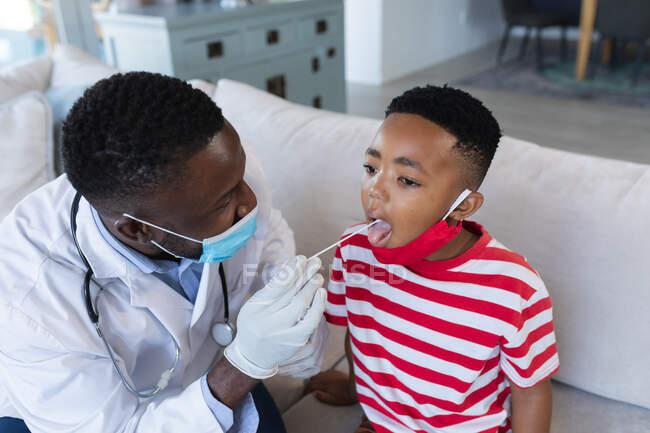 Medico afroamericano di sesso maschile che indossa maschera facciale dando covid test tampone al paziente ragazzo. medicinali, servizi sanitari e sanitari durante la pandemia di coronavirus covid 19. — Foto stock