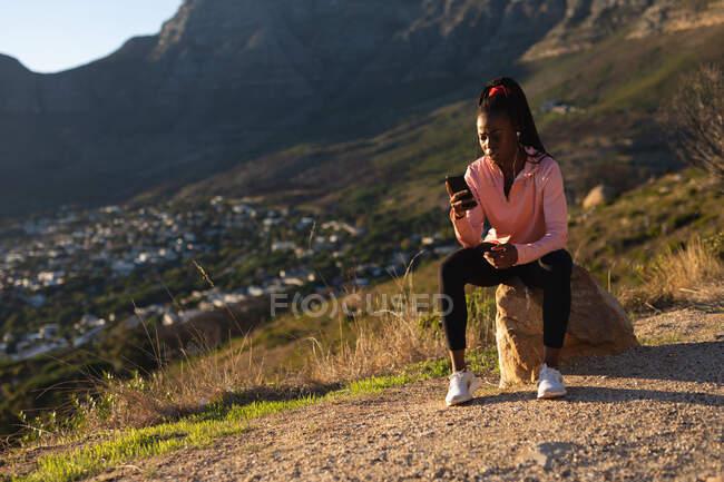 Donna afroamericana che si prende una pausa in esercizio all'aperto, indossando auricolari e utilizzando smartphone. sano stile di vita attivo e fitness all'aperto. — Foto stock