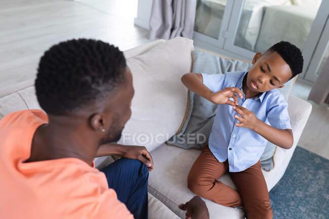 Африканский американец отец и сын сидят на диване, разговаривая дома в изоляции во время карантинной изоляции. — стоковое фото