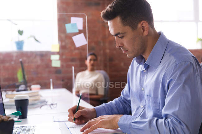 Hombre caucásico tomando notas mientras está sentado en su escritorio en la oficina moderna. negocio, profesionalidad y concepto de oficina - foto de stock