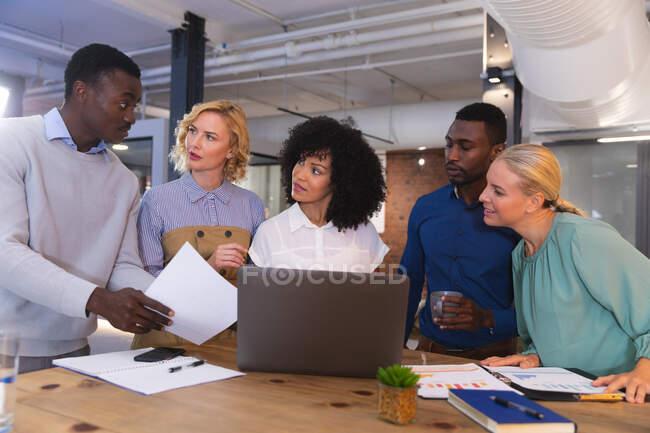 Команда різних офісних колег обговорює разом за ноутбуком у сучасному офісі. бізнес, професіоналізм, офіси та командна робота концепція — стокове фото